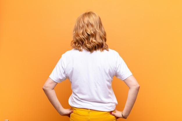 Zich verward of vol voelen of twijfels en vragen, afvragen, met de handen op de heupen, achteraanzicht
