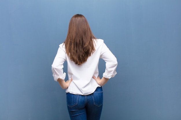 Zich verward of vol voelen of twijfels en vragen, zich afvragen, met handen op de heupen, achteraanzicht