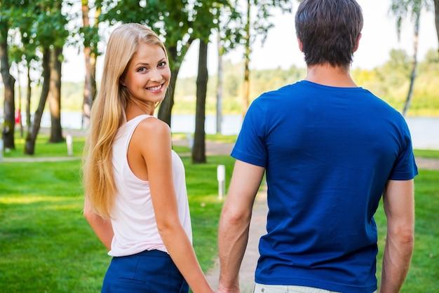 Zich zelfverzekerd en veilig bij hem in de buurt voelen. achteraanzicht van een mooie jonge vrouw die over de schouder kijkt en glimlacht terwijl ze met haar vriendje langs de parkweg loopt