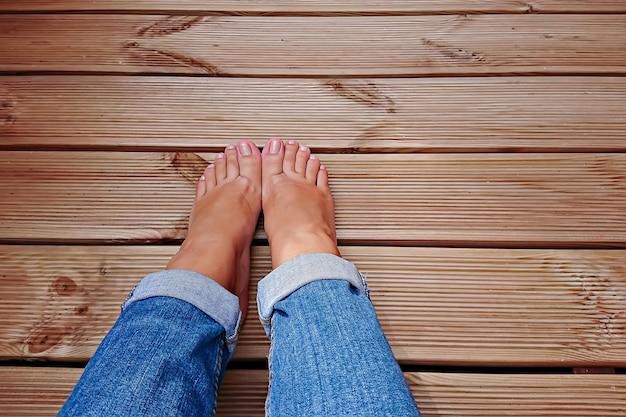 Zicht op de blote voeten van de vrouw in een blauwe spijkerbroek op een houten vloer