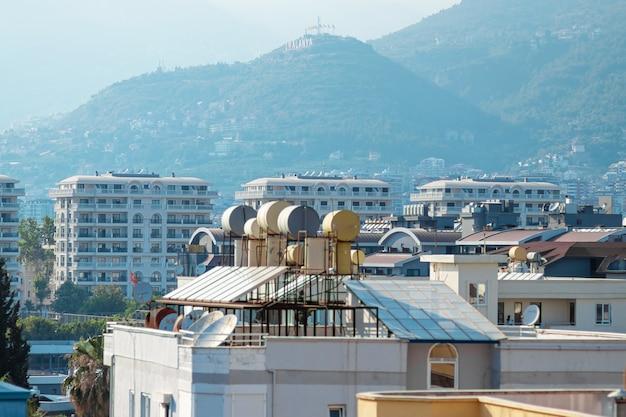 Zicht op de daken van huizen met zonnepanelen en watervaten. concept moderne technologieën, elektriciteitsbesparing.