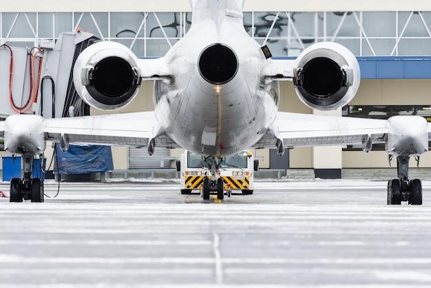 Zicht op de motoren en de staart van het vliegtuig bij terugduwen op de luchthaven.