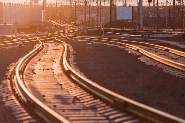 Zicht op de rails, betonnen dwarsliggers en heuvel van steenslag. het spoor.