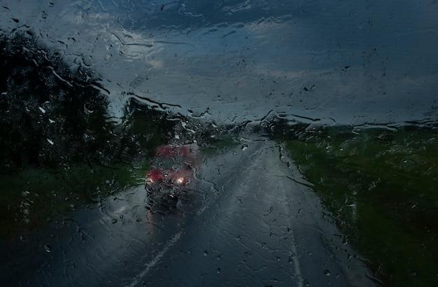 Zicht op de tegemoetkomende auto op de snelweg met de koplampen ingeschakeld door glas nat van zware regen in druppels en druppels bij zeer slecht weer in de avond