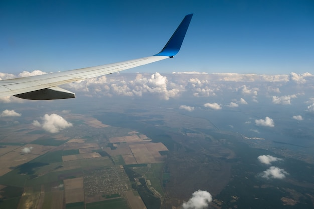 Zicht op de vleugel van het straalvliegtuig van binnenuit die over witte gezwollen wolken in de blauwe lucht vliegt. reizen en luchtvervoer concept.