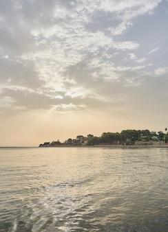 Zicht op de zon door de zonsopgangwolken op zee