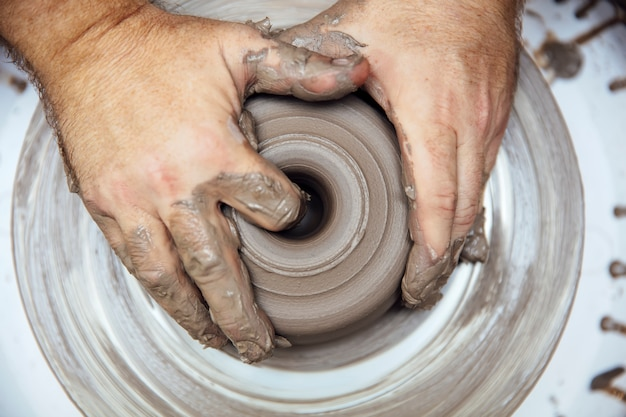 Zicht op een kunstenaar maakt aardewerk op een draaiwiel