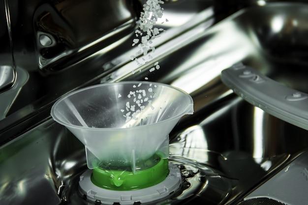 Zicht op het interieur van een lege geopende vaatwasser. onderhoud van huishoudelijke apparaten.