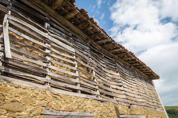 Zicht op oude schuur met stro opgeslagen achter een houten hek