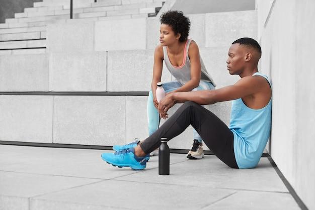 Zicht op peinzende jongeren hebben een sportieve lichaamsvorm, zijn gemotiveerd om gezond en fit te zijn, sporten in de open lucht, gaan de trap op, nemen pauze om water te drinken en op te frissen, zijn sterk. fitness concept