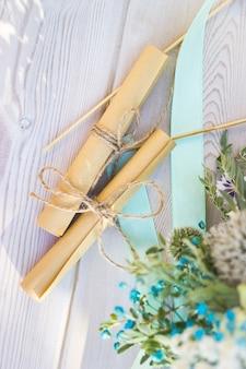 Zicht op twee opgerolde vellen papier met huwelijksgeloften hartvormige koekjes bisquites en boeket