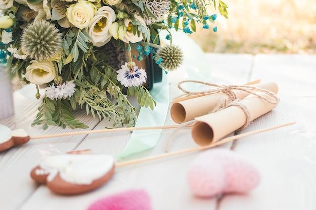 Zicht op twee opgerolde vellen papier met huwelijksgeloften hartvormige koekjes bisquites en bruidsboeket