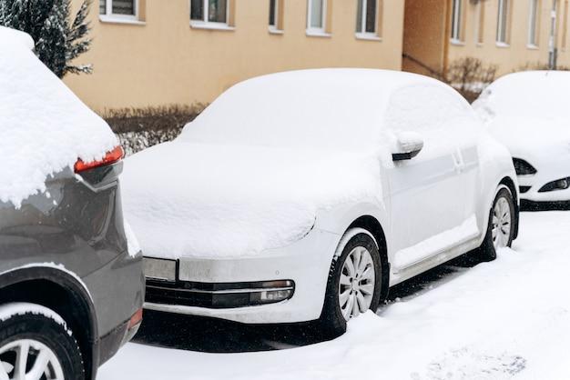 Zicht over de volledige lengte van de auto's die zijn opgelopen na een sneeuwcycloon. rijen van auto's die op een besneeuwde weg staan. winterconcept