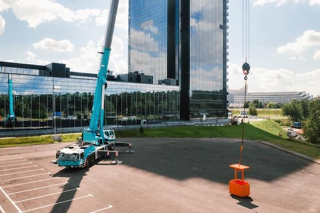 Zicht vanaf de hoogte van de auto van een zware kraan met wieg, die op de parkeerplaats open staat en klaar is om te werken. op het terrein staat de hoogste autokraan opgesteld.