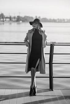 Zie er geweldig uit op elke leeftijd. een 40-jarige vrouw in een jas loopt langs de dijk.