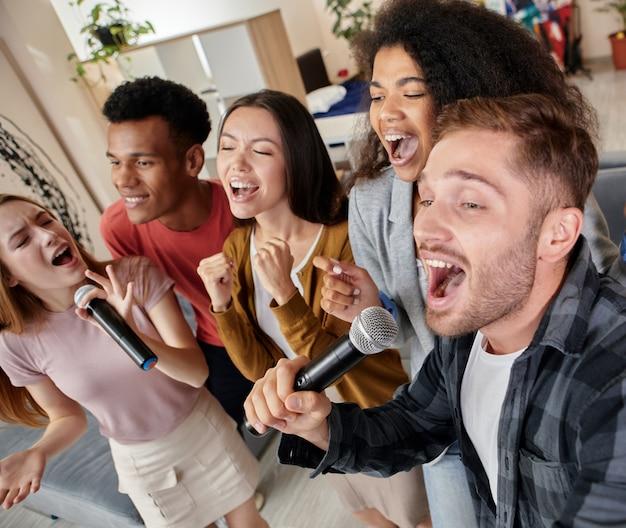 Zie het lied onder ogen van enthousiaste multiculturele vrienden die met microfoon zingen terwijl ze karaoke spelen bij