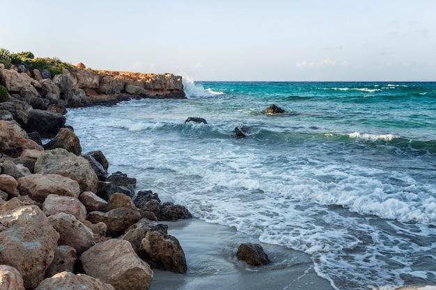 Ziedende blauwe zee met schuimende golven op een rotsachtige kust. wild strand, prachtige natuur.