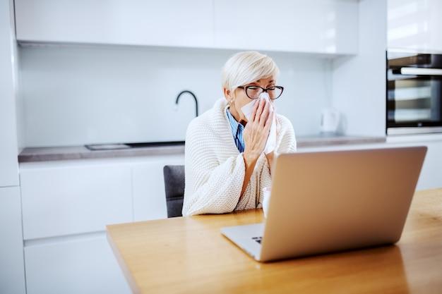 Ziek aantrekkelijke blonde senior vrouw bedekt met deken afvegen neus zittend aan eettafel