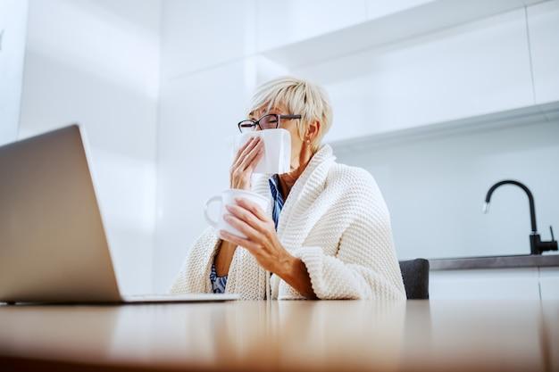 Ziek aantrekkelijke blonde senior vrouw bedekt met deken met mok met thee en neus afvegen zittend aan eettafel