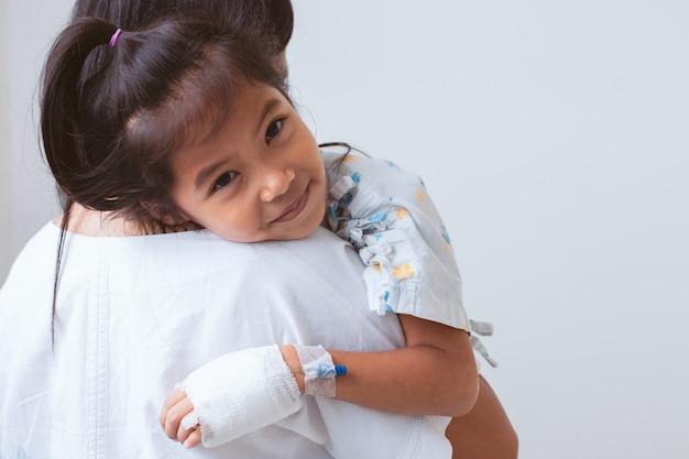 Ziek aziatisch kindmeisje dat iv-oplossing heeft verbonden die glimlachend en haar moeder in het ziekenhuis glimlacht