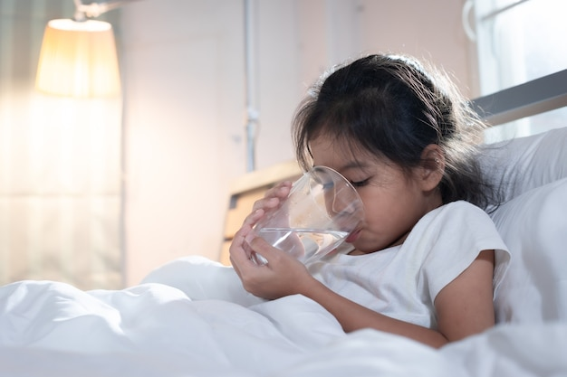 Ziek aziatisch kindmeisje drinkt water uit een glas na het eten van medicijnen in de slaapkamer.