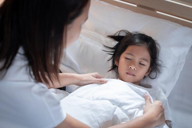 Ziek aziatisch kindmeisje wordt ziek en slaapt op het bed, moeder zorgt en bedekt de deken op haar dochter