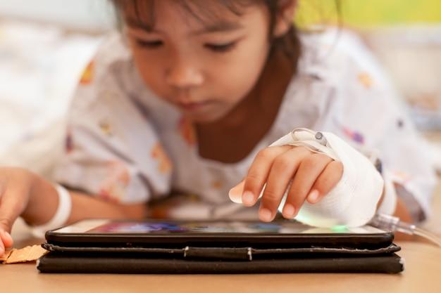 Ziek aziatisch klein kindmeisje die iv oplossing verbonden het spelen digitale tablet hebben