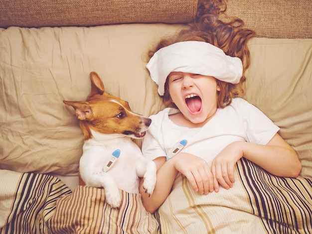 Ziek babymeisje en puppy onder dekbed