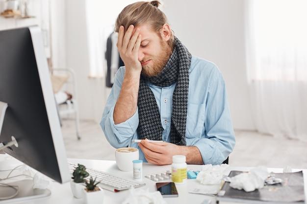 Ziek bebaarde man in wanhoop gebruikt thermometer om lichaamstemperatuur te meten, kijkt er helaas naar, lijdt aan hoge temperatuur, voelt zich slecht, omringd door medicijnen en zakdoeken op zijn werkplek.