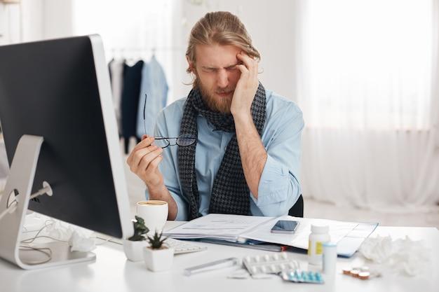 Ziek en moe bebaarde mannelijke student of kantoormedewerker heeft een slaperige uitdrukking, rent tempel vanwege misselijkheid, omringd door pillen en drugs, probeert zich te concentreren en het werk sneller af te maken