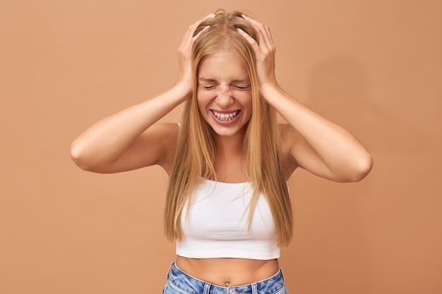 Ziek gefrustreerd tienermeisje dat haar ogen sluit, hoofd knijpt