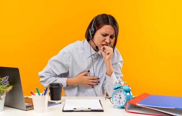 Ziek jong callcentermeisje die hoofdtelefoonszitting bij bureau dragen die en hand op borst zetten die op oranje wordt geïsoleerd