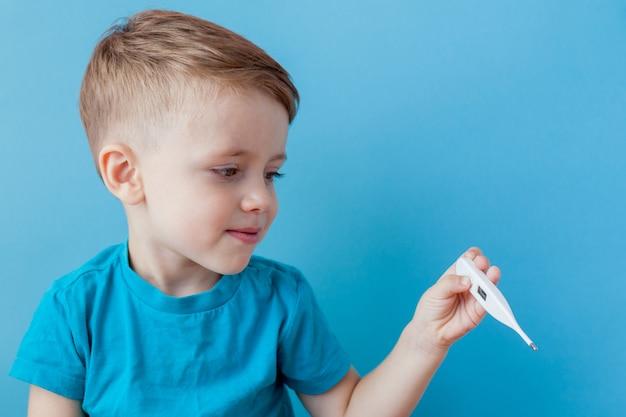 Ziek jong kind met een thermomether, het meten van de hoogte van zijn koorts en in de camera kijken