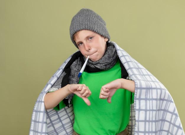 Ziek jongetje draagt groen t-shirt in warme sjaal en muts gewikkeld in deken thermometer aanbrengend mond meten temperatuur weergegeven: duimen naar beneden staande over lichte muur