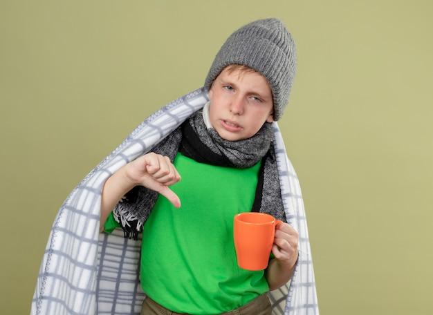 Ziek jongetje draagt groen t-shirt in warme sjaal en muts gewikkeld in een deken met kopje hete thee weergegeven: duimen naar beneden ongelukkig en ziek staande over lichte muur