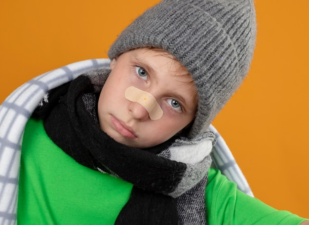 Ziek jongetje dragen warme muts en sjaal gewikkeld in een deken met patch op zijn neus ongelukkig en ziek kijken camera staande over oranje achtergrond