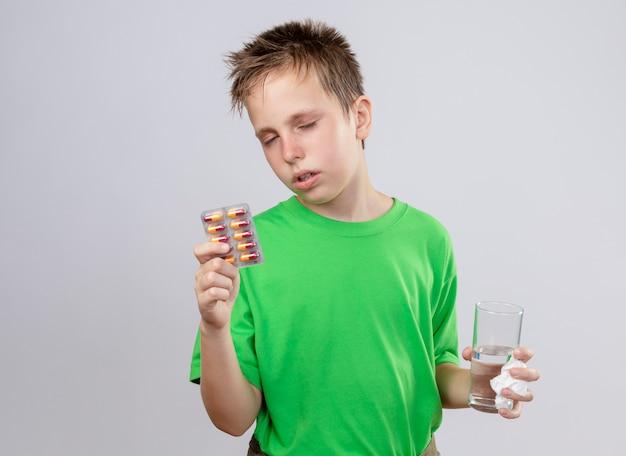 Ziek jongetje in groen t-shirt die zich onwel voelt met glas water en pillen die aan griep lijden die zich over witte muur bevinden