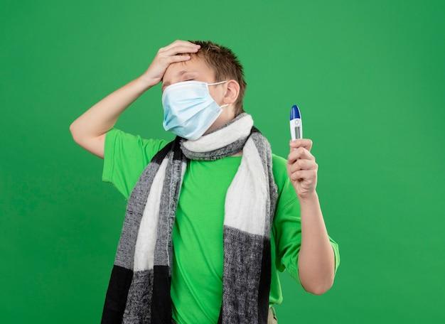 Ziek jongetje in groen t-shirt en warme sjaal om zijn dekkende gezichtsbeschermingsmasker terwijl hij een thremometer vasthoudt die verward en erg angstig kijkt met de hand op zijn hoofd die over de groene muur staat