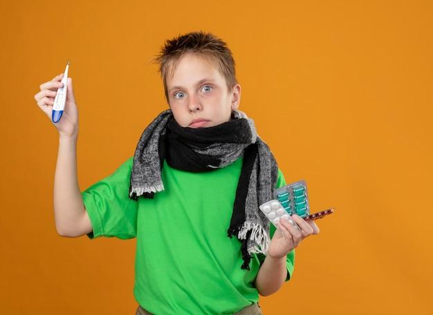 Ziek jongetje in groen t-shirt en warme sjaal om zijn nek met pillen die thremometer tonen die verward kijken over oranje muur