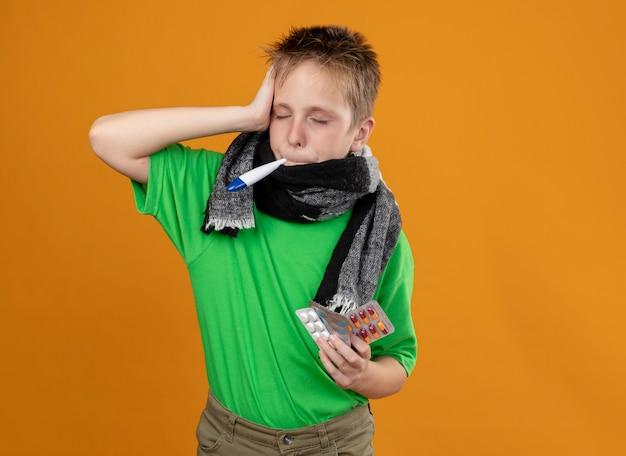 Ziek jongetje in groen t-shirt en warme sjaal om zijn nek met thermometer in zijn mond die pillen vasthoudt die onwel over oranje muur kijken