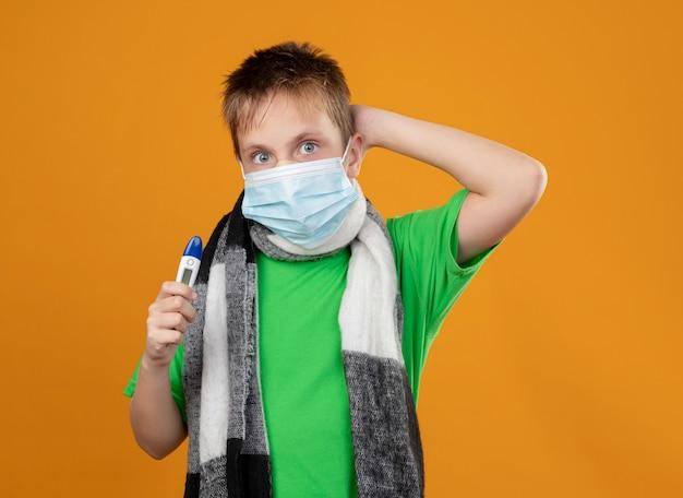 Ziek jongetje in groen t-shirt en warme sjaal rond zijn dekkende gezichtsbeschermend masker met thremometer lookign verward staande over oranje muur