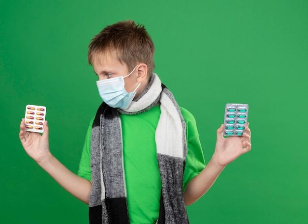 Ziek jongetje in groen t-shirt en warme sjaal rond zijn versleten gezicht beschermend masker met pillen op zoek verward proberen om een keuze te maken staande op groene achtergrond