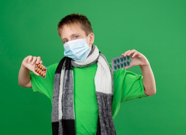 Ziek jongetje in groen t-shirt en warme sjaal rond zijn versleten gezichts beschermend masker met pillen kijken camera staande op groene achtergrond