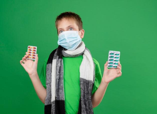 Ziek jongetje in groen t-shirt en warme sjaal rond zijn vervelend gezicht beschermend masker met pillen kijken staande over groene muur