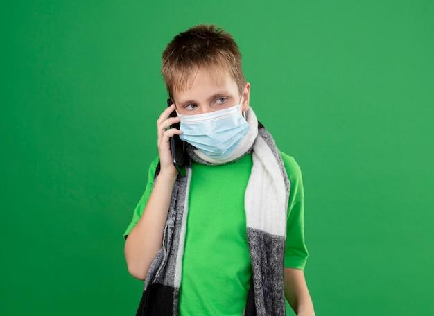 Ziek jongetje in groen t-shirt en warme sjaal rond zijn vervelend gezicht beschermend masker praten op mobiele telefoon staande over groene muur