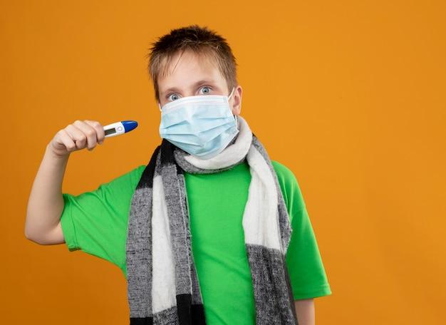 Ziek jongetje in groen t-shirt en warme sjaal rond zijn vervelend gezichtsbeschermend masker met thremometer op zoek bezorgd staande over oranje muur