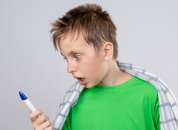 Ziek jongetje in groen t-shirt gewikkeld in deken onwel gevoel houden thermometer kijken verbaasd staande over witte muur