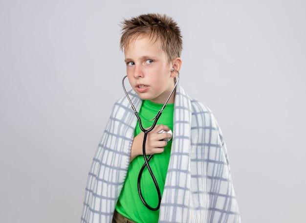 Ziek jongetje in groen t-shirt gewikkeld in deken onwel voelen met een stethoscoop om zijn nek luisteren naar de hartslag die verward is staande over een witte muur