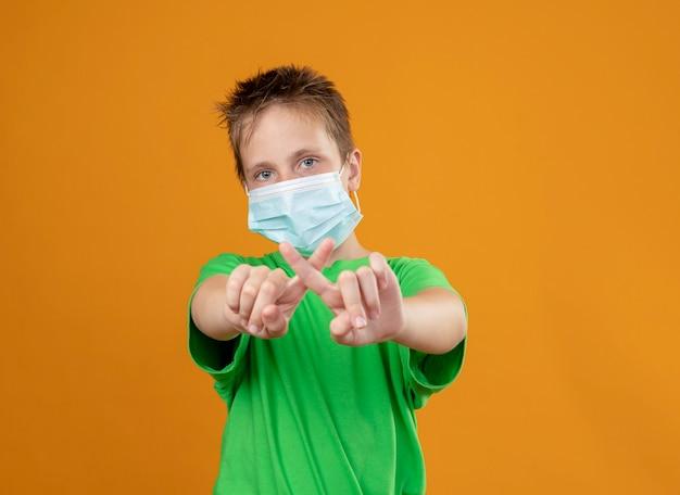 Ziek jongetje in groen t-shirt met gezichts beschermend masker maken stop gebaar kruising wijsvingers staande over oranje muur