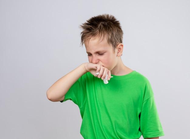 Ziek jongetje in groen t-shirt zich onwel voelen lijdt aan loopneus en griep die zich over witte muur bevindt